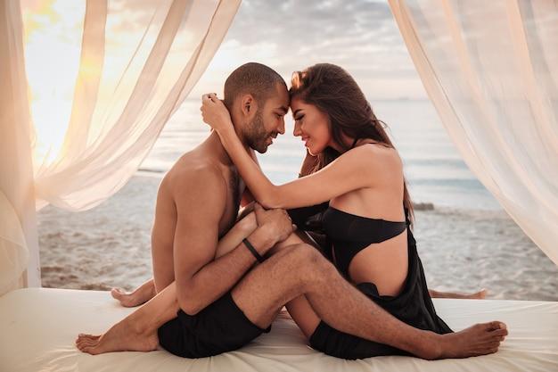 Feliz pareja joven sentada y abrazándose en la cama en la playa