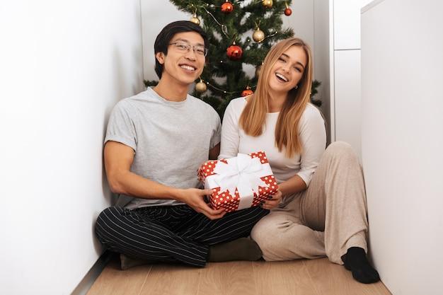 Feliz pareja joven, sentada en el árbol de navidad, sosteniendo una caja de regalo en casa