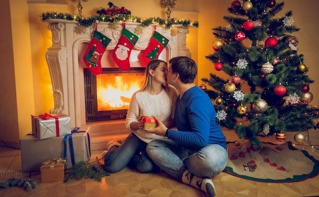Feliz pareja joven sentada en la chimenea y besándose en la víspera de navidad