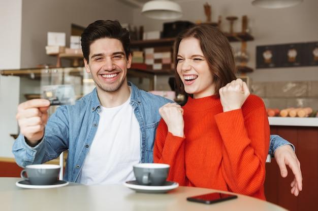 Feliz pareja joven sentada en la mesa de café