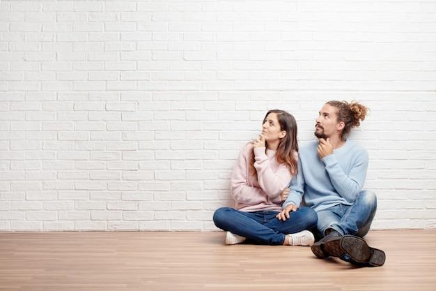 Feliz pareja joven sentada en el piso de su nueva casa. conc