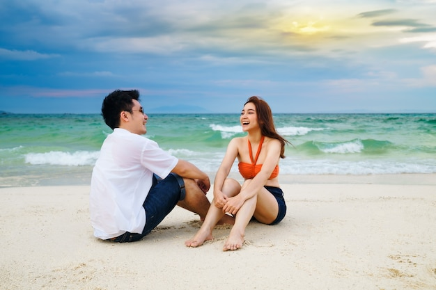 Feliz pareja joven sentada en la playa del mar en la isla de koh munnork, rayong, tailandia