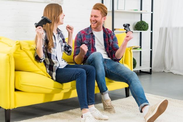 Feliz pareja joven sentada en un sofá amarillo apretando su puño como ganador después de jugar el videojuego