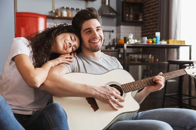 Feliz pareja joven sentada en el sofá en casa y tocando música en la guitarra acústica