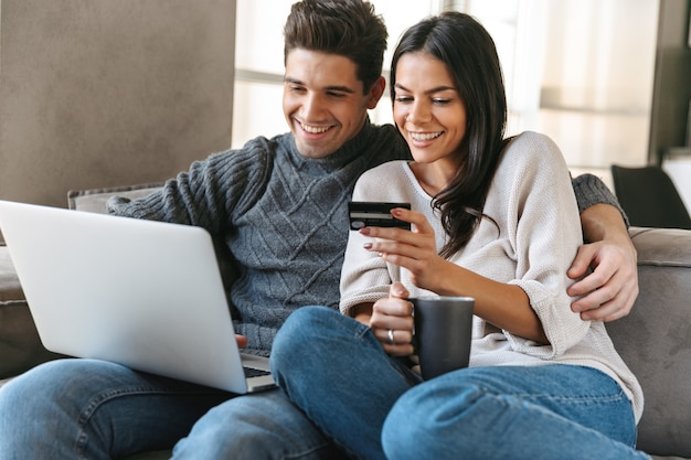 Feliz pareja joven sentada en un sofá en casa, utilizando equipo portátil