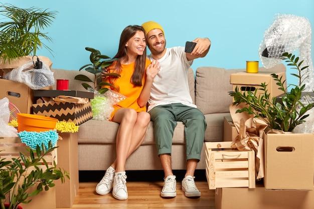 Feliz pareja joven sentada en el sofá rodeado de cajas