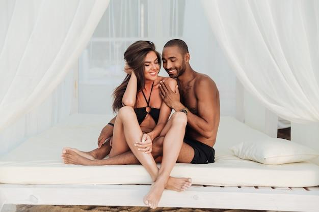 Feliz pareja joven sentada y sonriendo en la cama blanca en la playa