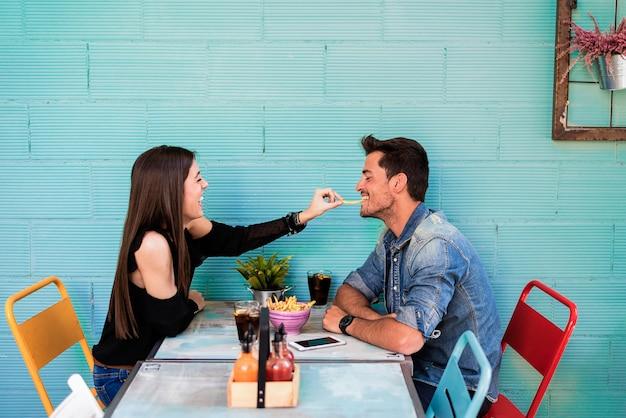 Feliz pareja joven sentado en un restaurante