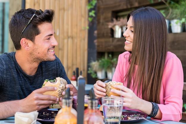 Feliz pareja joven sentado en la terraza de un restaurante comiendo una hamburguesa