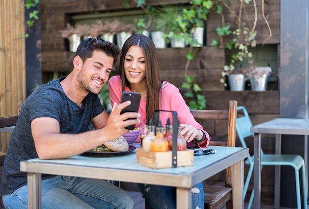 Feliz pareja joven sentado en la terraza de un restaurante con un teléfono inteligente
