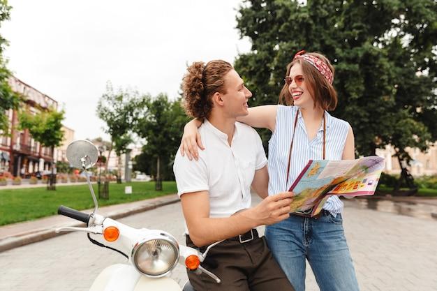Feliz pareja joven sentados juntos en moto en la calle de la ciudad, analizando el mapa guía de la ciudad