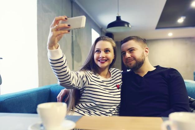 Feliz pareja joven con smartphone tomando selfie en café en el centro comercial