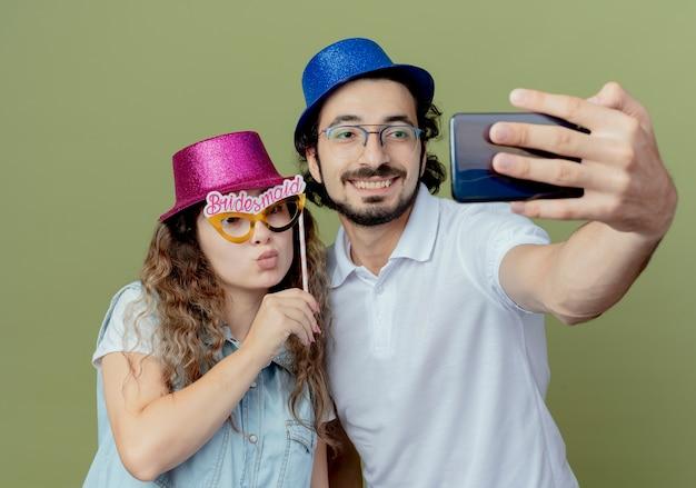 Feliz pareja joven con sombrero rosa y azul tomar un selfie y niña sosteniendo máscara de ojos de mascarada en el palillo
