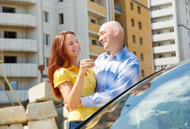 Feliz pareja joven sonriente mostrando un par de llaves de su nueva casa