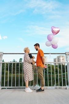 Feliz pareja joven sonriente se reúne en el puente sosteniendo globos rosas y perro con ciudad en el horizonte