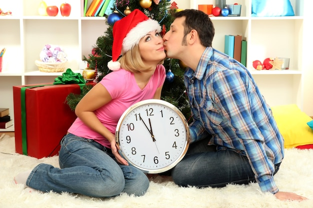 Feliz pareja joven sosteniendo el reloj cerca del árbol de navidad en casa