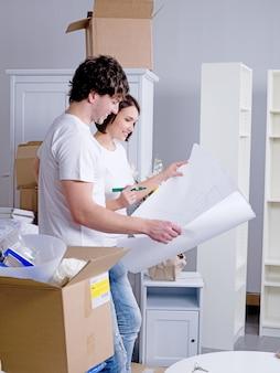 Feliz pareja joven en su nuevo piso con plan en sus manos