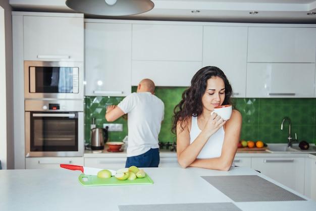 Feliz pareja joven tomando un café en la cocina