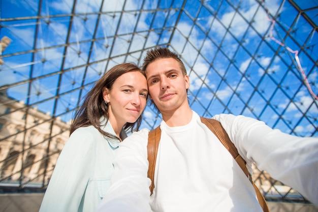Feliz pareja joven tomando selfie en parís en vacaciones europeas