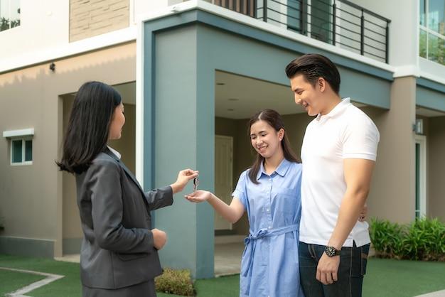 Feliz pareja joven tomar las llaves de la nueva casa grande del agente inmobiliario