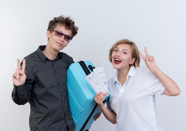 Feliz pareja joven de turistas hombre y mujer con maleta y billetes de avión sonriendo mostrando signo v sobre blanco