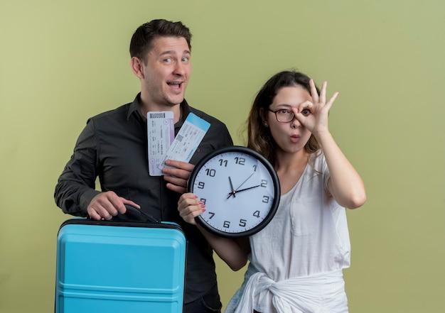 Feliz pareja joven de turistas hombre sujetando la celebración de billetes de avión y maleta con mujer sosteniendo reloj de pared haciendo ok cantar sobre la luz