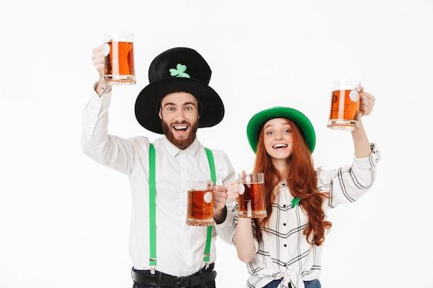 Feliz pareja joven vestida con disfraces, celebrando el día de san patricio aislado sobre una pared blanca, bebiendo cerveza