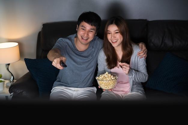 Feliz pareja joven viendo la televisión en el sofá por la noche