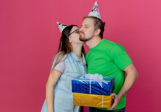 Feliz pareja joven vistiendo gorro de fiesta chica besando al hombre con cajas de regalo aisladas en la pared rosa