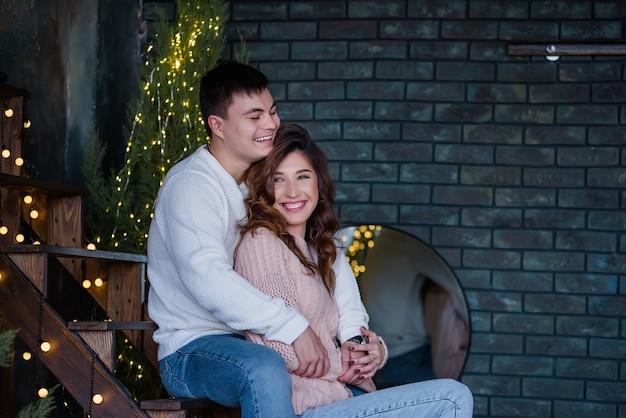 Feliz pareja joven vistiendo ropa de invierno en la habitación decorada con luces de navidad