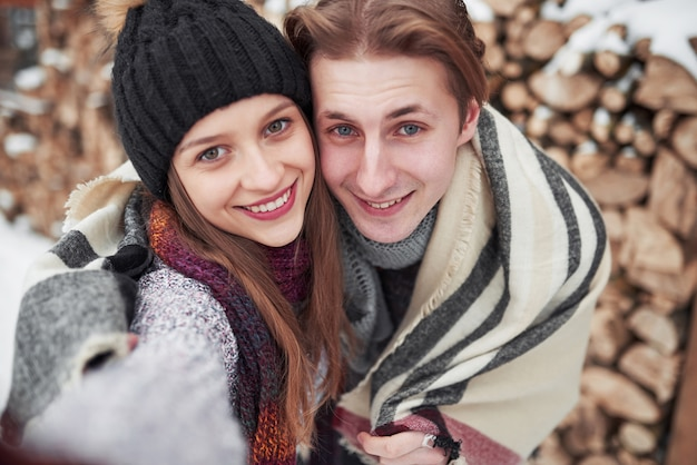 Feliz pareja joven en winter park divirtiéndose. familia al aire libre.