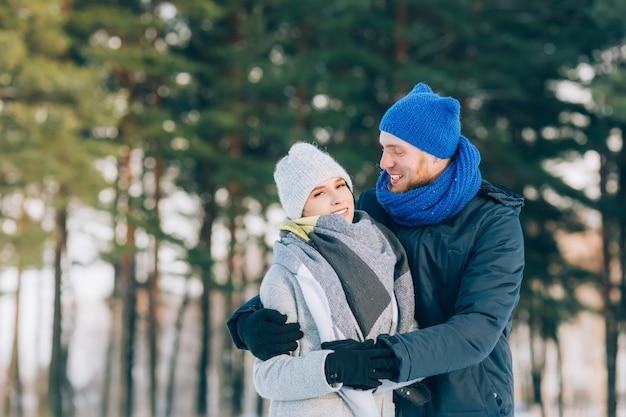 Feliz pareja joven en winter park riendo y divirtiéndose