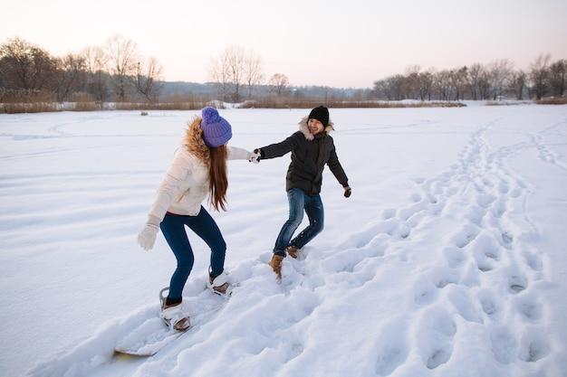 Feliz pareja de jóvenes se divierten en la estación de esquí en un día de invierno cubierto de nieve.