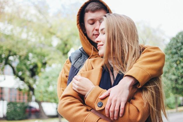 Feliz pareja de jóvenes enamorados adolescentes amigos vestidos de estilo casual en la calle de la ciudad de otoño