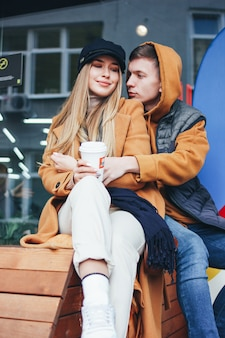 Feliz pareja de jóvenes enamorados adolescentes amigos vestidos de estilo casual caminando juntos en la calle de la ciudad en temporada fría