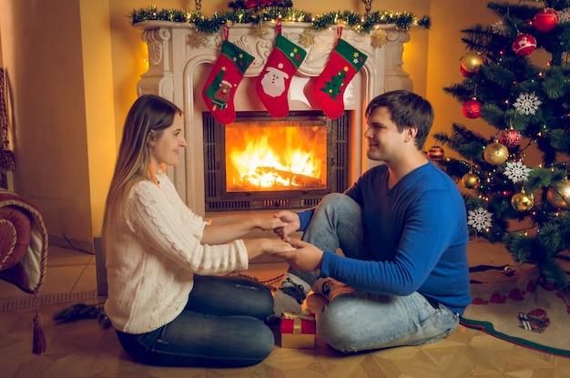 Feliz pareja de jóvenes enamorados sentados en la chimenea y tomados de la mano