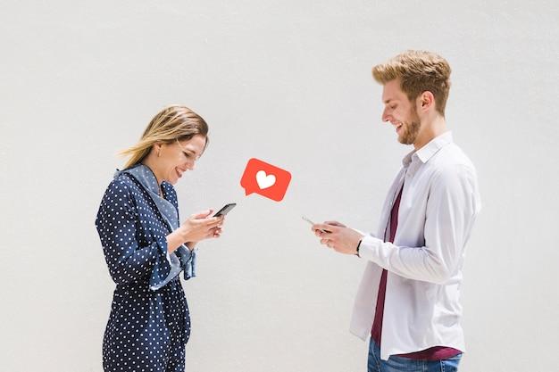 Feliz pareja de jóvenes intercambiando mensajes de amor