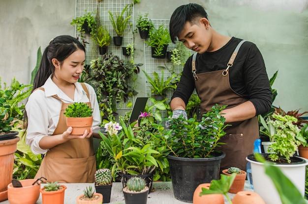 Feliz pareja de jóvenes jardineros asiáticos vistiendo delantal utiliza equipo de jardín y computadora portátil para cuidar
