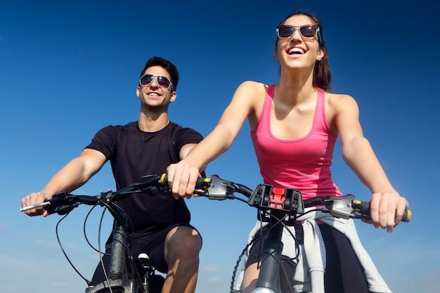 Feliz pareja de jóvenes en un paseo en bicicleta en el campo