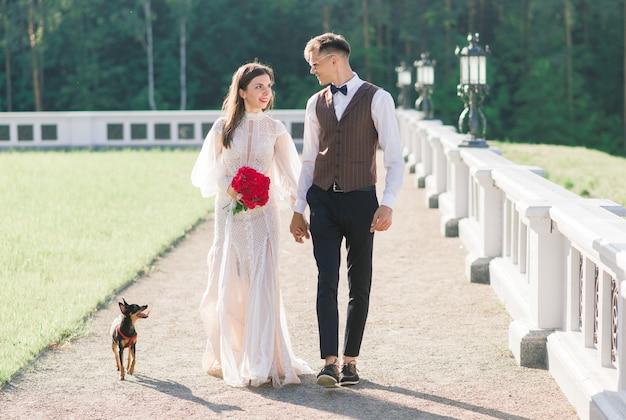 Feliz pareja de jóvenes recién casados celebrando y divertirse al aire libre