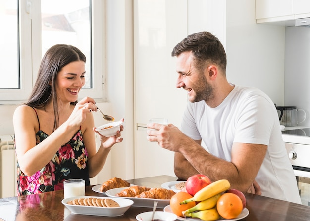 Feliz pareja de jóvenes sentados en la cocina desayunando