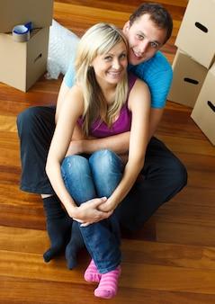 Feliz pareja de jóvenes sentados en el piso