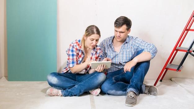 Feliz pareja de jóvenes sentados en el suelo y elegir muebles para su nueva casa en proceso de renovación.
