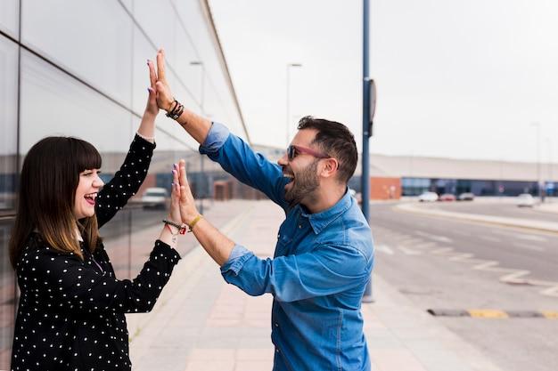 Feliz pareja de jóvenes tocando las palmas de los demás en la calle