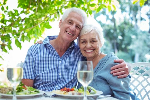 Feliz pareja de jubilados con el brazo alrededor en la mesa