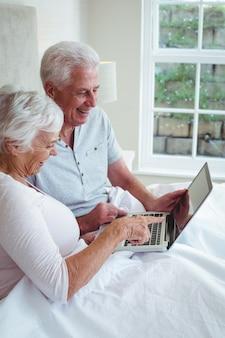 Feliz pareja de jubilados con laptop