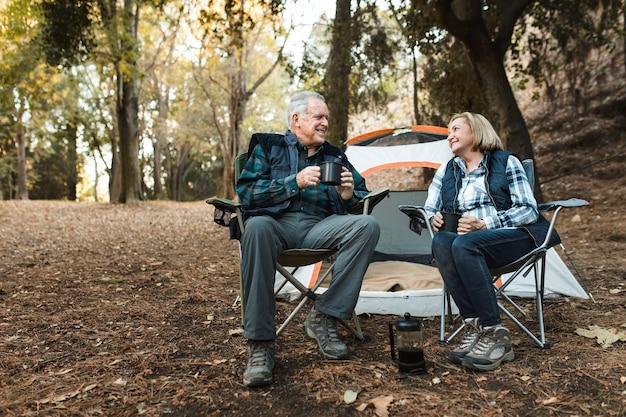 Feliz pareja de jubilados tomando un café junto a la carpa en el bosque