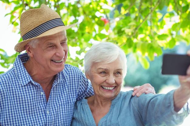 Feliz pareja de jubilados tomando selfie