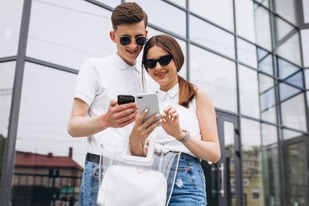 Feliz pareja juntos en la ciudad usando el teléfono