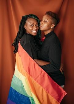 Feliz pareja de lesbianas con una bandera de colores